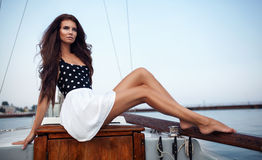 Vintage portrait of beautiful pretty woman sitting on the board. Of yacht Royalty Free Stock Photo