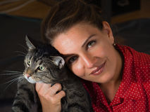 Vintage portrait of a beautiful young woman in a red dress and a. Cute cat Royalty Free Stock Photos