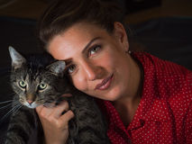 Vintage portrait of a beautiful young woman in a red dress and a. Cute cat Stock Image