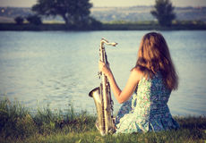 Vintage portrait of a beautiful young woman sitting on the riverbank with a sax Stock Photo