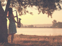 Vintage portrait of a beautiful young woman standing near a tree on the riverbank with a sax Stock Photos