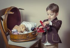 Vintage portrait of boy playing with tin toys Stock Photos