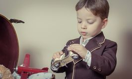 Vintage portrait of boy playing with tin toys Royalty Free Stock Image