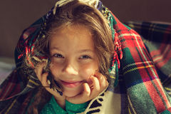 Vintage Portrait of cute adorable smiling little girl look out from red plaid Royalty Free Stock Photo