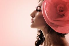 Vintage portrait of fashion glamour girl with red flower in her. Hair. Studio shot, tonned Royalty Free Stock Photo