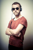 Vintage portrait of fashion guy with headphones and sunglasses Stock Image