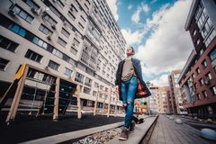 Guy with tattoos smokes cigarettes on the street, walks in the city on the street among high-rise buildings. Vintage portrait of handsome serious thoughtful Royalty Free Stock Photography