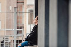 Guy with tattoos smokes cigarettes on the street, walks in the city on the street among high-rise buildings. Vintage portrait of handsome serious thoughtful Royalty Free Stock Images