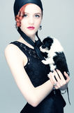 Vintage portrait of a lady with a puppy. Studio photo of a young red-haired girl with a black and white puppy Stock Photos