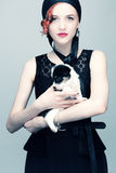 Vintage portrait of a lady with a puppy. Studio photo of a young red-haired girl with a black and white puppy Royalty Free Stock Images