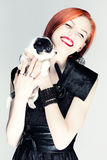 Vintage portrait of a lady with a puppy. Studio photo of a young red-haired girl with a black and white puppy Stock Image