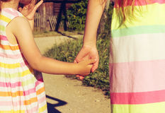 Vintage portrait of little girls holding hand in hand in summer day outdoors Royalty Free Stock Photography