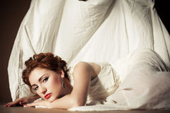 Vintage portrait of a red-haired girl in white. Vintage portrait of a glamourous queen like girl in bedroom. Retro style. Daylight. Studio shot Royalty Free Stock Photos