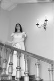 Vintage portrait of a young woman walking down the stairs Stock Photo