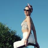 Vintage positive gir. L in sunglasses enjoying life. On background blue sky Stock Photo