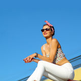 Vintage positive gir. L in sunglasses enjoying life. On background blue sky Royalty Free Stock Photography