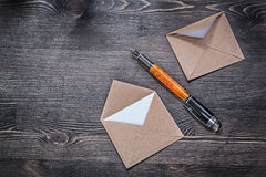Vintage post envelope fountain pen on wooden board directly abov Royalty Free Stock Photo