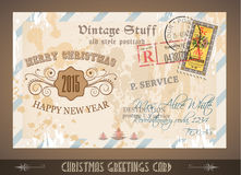 Vintage Postacard for Christmas greetings cards. With postage stamps and festive text with fake address. Retro design with distressed old look Royalty Free Stock Photography