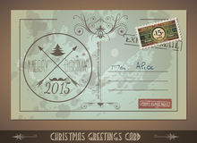Vintage Postacard for Christmas greetings cards. With postage stamps and festive text with fake address. Retro design with distressed old look Royalty Free Stock Photo