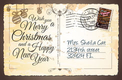 Vintage Postacard for Christmas greetings cards. With postage stamps and festive text with fake address. Retro design with distressed old look Stock Images