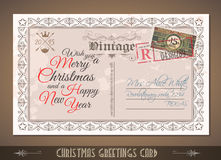 Vintage Postacard for Christmas greetings cards. With postage stamps and festive text with fake address. Retro design with distressed old look Royalty Free Stock Image