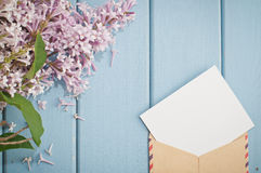 Vintage postage envelope with card and summer bouquet of lilac Stock Photography