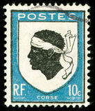 Vintage postage stamp from Corsica. Vintage postage stamp with Corsica national emblem of a Moorish head Stock Image
