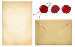Vintage postal set: envelope, paper and wax seals. Vintage postal set: old mail envelope, blank letter paper and red wax seal stamps isolated on white Royalty Free Stock Image