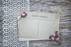 Vintage postcard, lace fabric and dry tea roses on the old wood Stock Photo