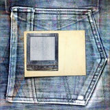 Vintage postcard with paper slides on old jeans Stock Photography