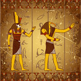 Vintage poster with egyptian gods on the grunge background with silhouettes of the ancient egyptian hieroglyphs. Stock Image