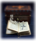 Vintage Prayer Book & Rosary. Still life of a rosary spilling out of a wooden box onto an open old prayer book Stock Image