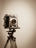 Vintage Press Camera on Wooden Tripod. Sepia toned image of a classic old 4 x 5 press camera on a wooden tripod Royalty Free Stock Image