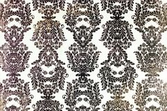 Vintage printed damask repeat pattern. A closeup of an old fashioned shabby white and black damask flower pattern printed on a paper background Stock Image