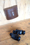 Vintage prism black color binoculars and brown leather case on the wall Stock Images