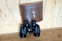 Vintage prism black color binoculars and brown leather case on the wall Royalty Free Stock Images