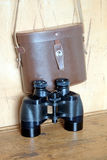 Vintage prism black color binoculars and brown leather case on the wall. Vintage Porro prism black color military binoculars and closed brown hard leather case stock photography