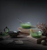 Vintage, Provence sopa de la espinaca en un bol de vidrio en la tabla rústica áspera microprocesadores, huevo de codornices, flor Fotos de archivo libres de regalías