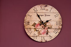 Vintage purple clock. Vintage clock on purple wall background Royalty Free Stock Image