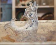 Vintage que decora em uma loja de antiguidades com uma cabeça italiana pintada velha da fonte do golfinho do cimento Fotografia de Stock Royalty Free