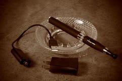 Vintage que mira el cigarrillo electrónico con el cargador Imagen de archivo libre de regalías