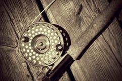Vintage que mira la pesca con mosca Rod de la sepia en la madera Imagenes de archivo