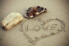 Vintage que mira la sandalia de la sepia y el mensaje de cuero del amor en arena Fotos de archivo libres de regalías