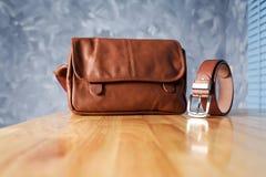 Vintage que viaja para los accesorios del ` s de los hombres, el bolso marrón y la correa puestos Foto de archivo libre de regalías