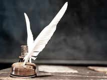 Feather quill pen and ink bottle, desaturated composition royalty free stock photography