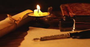 Vintage quill pen and inkwell on old parchment paper in candlelight