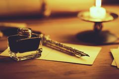 Vintage quill pen and inkwell on wooden table in candlelight royalty free stock images