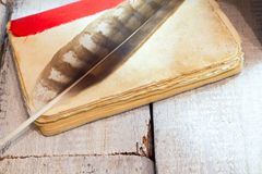 Vintage quill pen on old book. top view. stock image