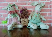 Vintage rabbit dolls sitting on a wooden floor royalty free stock images
