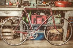 Vintage racing bycicle in front of an old work bench with tools stock images